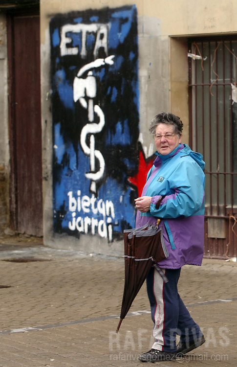 A woman stands close to a graffiti representing the pro-independence armed Basque group ETA logo, 23 March 2006 in the northern Spanish village of Alsasua, Navarra province. PHOTO RAFA RIVAS