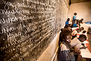 Teacher Fabrice teaches the day's lesson in an over-crowded schoolroom in the Genocide survivors village of Rugerero Rwanda.