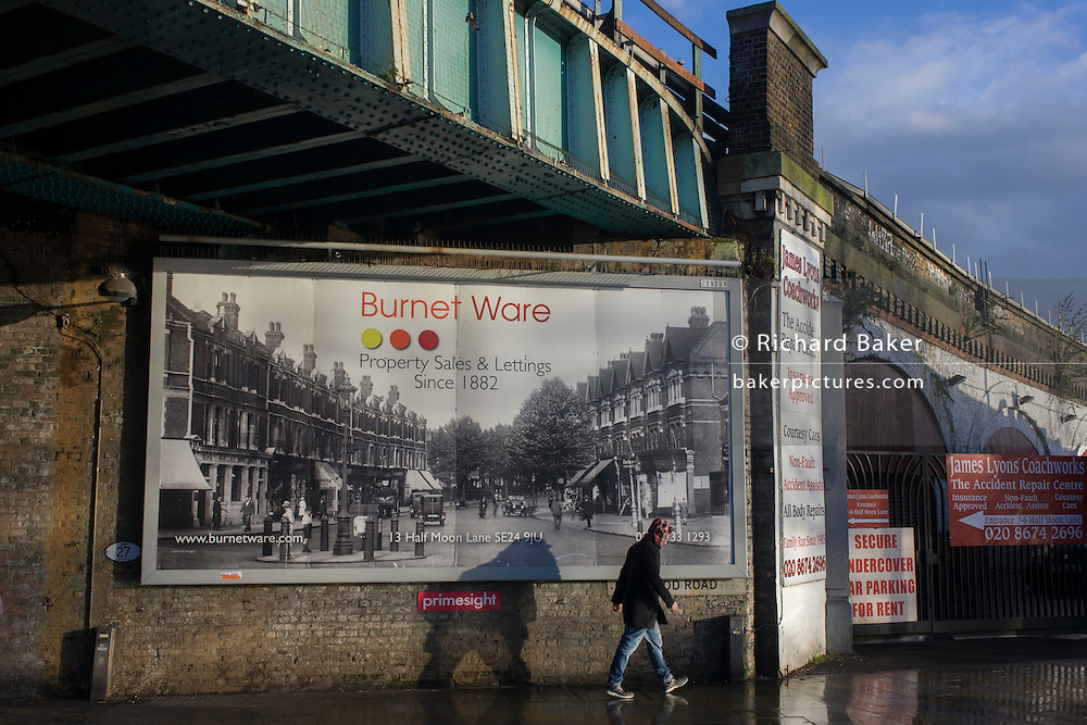 Property estate agent's billboard showing old street scene under railway bridge in Herne Hill, South London SE24.