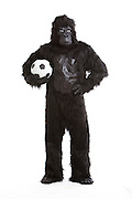 Young man in gorilla costume holding soccer ball against white background