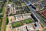 Nederland, Noord-Holland, Amsterdam, 14-06-2012; de nieuwe wijk Laan van Spartaan, met sportvelden. Rechts de Ring A10, Einsteinweg. Boven in beeld Kolenkitbuurt en kerk De Kolenkit (Opstandingskerk) en Poortgebouw. Vlnr de Eramusgracht...A10 Ring roadway and new constructed residential district Laan van Spartaan (l) with playing fields in Amsterdam-west. The church (m, t) next to the roadway is nicknamed Kolenkit (coal-hod) and so this district is called the Coal-hod district. luchtfoto (toeslag), aerial photo (additional fee required).foto/photo Siebe Swart