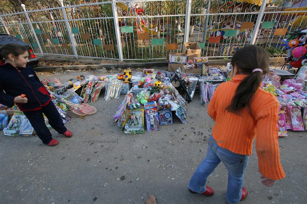 Zwei Mädchen begutachten die Auslagen eines Freiluft-Spiele-Ladens in Machatschkala, Dagestan. Two yound girls check out the offers of an oper sky game shop in Makhachkala, Dagestan.