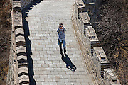 Tourist takes a photograph on the ancient Great Wall of China at Mutianyu, north of Beijing (formerly Peking), China