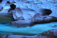 Pre-dawn blue light turn the wave like rocks and swirling water of the Babinda Boulders into abstract art.