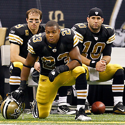 November 6, 2011; New Orleans, LA, USA; New Orleans Saints players running back Pierre Thomas (23), quarterback Drew Brees (9) and quarterback Chase Daniel (10) look on from the sideline as trainers check on cornerback Tracy Porter (not pictured) who injured his neck during the first quarter of a game against the Tampa Bay Buccaneers at the Mercedes-Benz Superdome. Mandatory Credit: Derick E. Hingle-US PRESSWIRE
