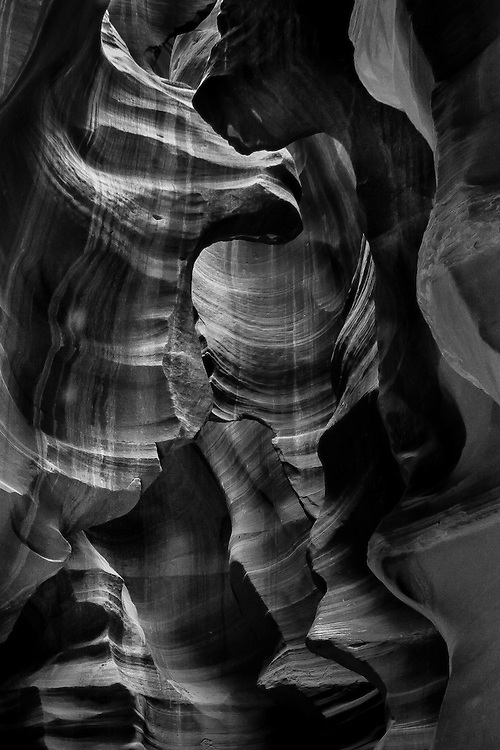 Black and white photograph of strange shapes and shadows in the sculpted stone in Upper Antelope Canyon near Page, AZ