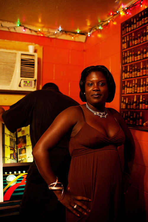 A woman poses for a portrait while a man selects a new song from the jukebox at Odessa's Place, a one-room bar in the Baptist Town neighborhood of Greenwood, Mississippi on Friday, July 2, 2010.