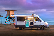 White Remodeled Conversion Van on the Beach at Sunset