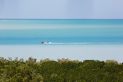 A recreational fishing vessel heads up Dampier Creek in Broome's Roebuck Bay.