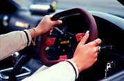 A girl with false nails, with her hands on the steering wheel of her car, Girlracers, Southend, UK 2004