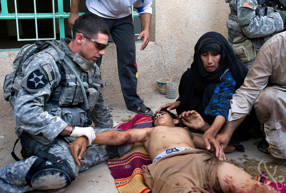 U.S. Army 3-2 Strykers medic, Specialist Daniel Witt, from Huntsville, TX gives first aid to an Iraqi boy injured collaterally during a continued assault on Al Qaeda fighters in the Iraqi city of Bacouba June 20, 2007. The boy suffered severe leg injuries when a U.S. fired smoke screen shell exploded near him on a street corner..