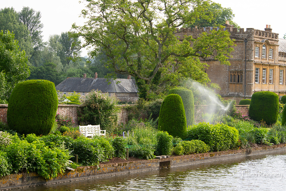 A sprinkler in the herbaceous borders next to the long pond at Forde Abbey, Chard, Dorset, UK