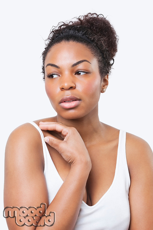 Thoughtful African American young woman looking away over white background