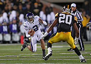 October 15, 2011: Northwestern Wildcats quarterback Kain Colter (2) tries to avoid Iowa Hawkeyes linebacker Christian Kirksey (20) during the first half of the NCAA football game between the Northwestern Wildcats and the Iowa Hawkeyes at Kinnick Stadium in Iowa City, Iowa on Saturday, October 15, 2011. Iowa defeated Northwestern 41-31.