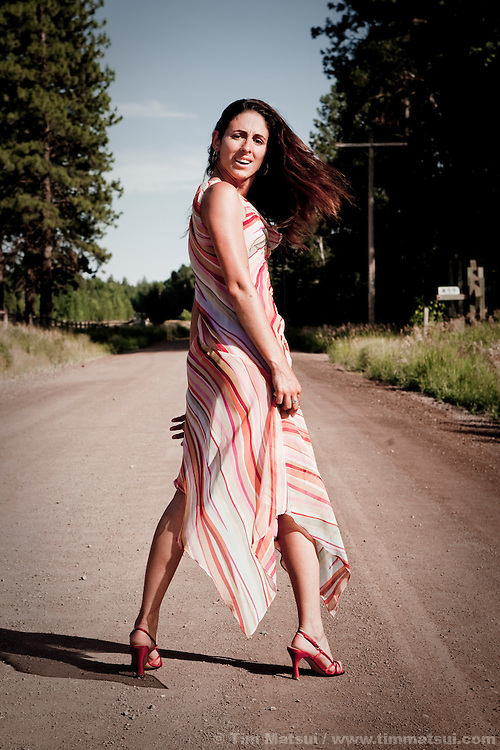 A beautiful young latina woman struts and turns in a dress and heels on a rural dirt road.