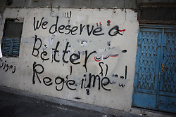 Anti-government graffiti covers the walls in Sanabis. It's often removed by security forces, and painted on again by activists