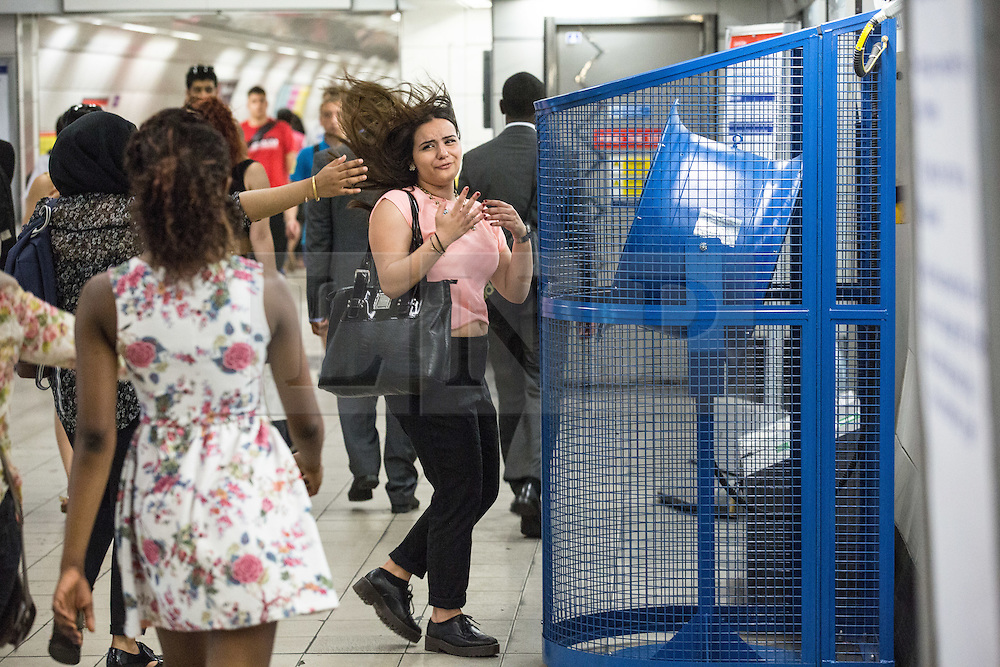 © Licensed to London News Pictures. 01/07/2015. London, UK. A woman takes a moment to enjoy a fan at Bank Station on a morning in which commuters and tourists struggle with the intense heat on the London Underground this morning (01/07) on what is set to be the hottest day this decade. Photo credit : James Gourley/LNP
