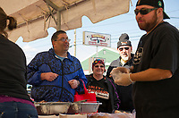 Mike Joslin served up burgers and hot dogs at Sanborn's Auto Repair on Saturday for Lucky Jr's birthday party.  (Karen Bobotas/for the Laconia Daily Sun)