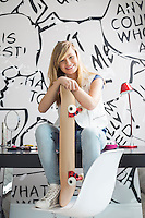 Full-length portrait of happy teenage girl with skateboard sitting on study table at home