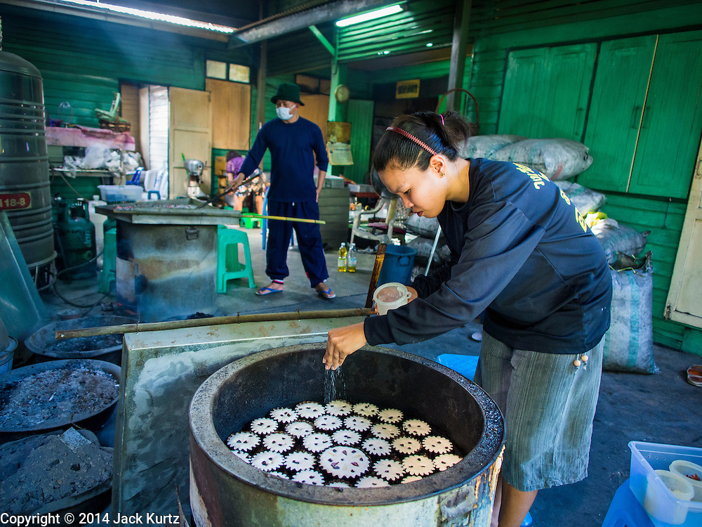 "28 OCTOBER 2014 - BANGKOK, THAILAND: A worker sprinkles sugar on top of cakes in a traditional oven at the Pajonglak Maneeprasit Bakery in Bangkok. The cakes are called ""Kanom Farang Kudeejeen"" or ""Chinese Monk Candy."" The tradition of baking the cakes, about the size of a cupcake or muffin, started in Siam (now Thailand) in the 17th century AD when Portuguese Catholic priests accompanied Portuguese soldiers who assisted the Siamese in their wars with Burma. Several hundred Siamese (Thai) Buddhists converted to Catholicism and started baking the cakes. When the Siamese Empire in Ayutthaya was sacked by the Burmese the Portuguese and Thai Catholics fled to Thonburi, in what is now Bangkok. The Portuguese established a Catholic church near the new Siamese capital. Now just three families bake the cakes, using a recipe that is 400 years old and contains eggs, wheat flour, sugar, water and raisins. The same family has been baking the cakes at the Pajonglak Maneeprasit Bakery, near Santa Cruz Church, for more than 245 years. There are still a large number of Thai Catholics living in the neighborhood around the church.   PHOTO BY JACK KURTZ"