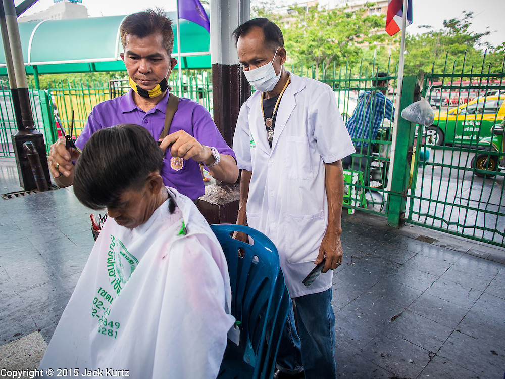 16 APRIL 2015 - BANGKOK, THAILAND: The instructor works on a traveler's hair at a barber school that sets up on the platform at Hua Lamphong Train Station in Bangkok. Travelers get free haircuts and the barber students get to practice on real heads.    PHOTO BY JACK KURTZ