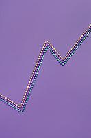 Mardi Gras beads on purple background