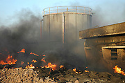 Fire flames and smoke in an old deserted factory now illegally used as a rubbish dump
