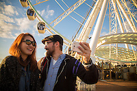 Seattle, Washington- September 30, 2014: A couple captures a selfie in front of the Seattle Great Wheel. The 175-foot ferris wheel opened in 2012 and offers spectacular views of Elliott Bay and the Seattle skyline. It is the largest observation wheel on the west coast. CREDIT: Chris Carmichael for the New York Times