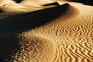 Desert sand dunes with dark shadows in the Sahara desert of Morocco.