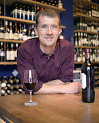 Man leaning on counter with a glass and bottle of red wine, France