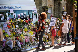 © Licensed to London News Pictures. 19/06/2017. London, UK. Member of the public observe flowers left at Grenfell tower block in Notting Hill following a huge fire last week.  The blaze engulfed the 27-storey building killing dozens - with dozens of people still in hospital, many of whom are in critical condition. Photo credit: Ben Cawthra/LNP