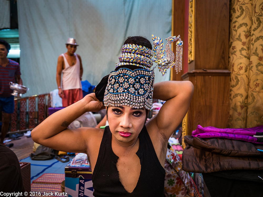 "30 JANUARY 2016 - NONTHABURI, NONTHABURI, THAILAND: A performer puts on his stylized hat before a ""likay"" show at Wat Bua Khwan in Nonthaburi, north of Bangkok. Likay is a form of popular folk theatre that includes exposition, singing and dancing in Thailand. It uses a combination of extravagant costumes and minimally equipped stages. Intentionally vague storylines means performances rely on actors' skills of improvisation. Like better the known Chinese Opera, which it resembles, Likay is performed mostly at temple fairs and privately sponsored events, especially in rural areas. Likay operas are televised and there is a market for bootleg likay videos and live performance of likay is becoming more rare.     PHOTO BY JACK KURTZ"