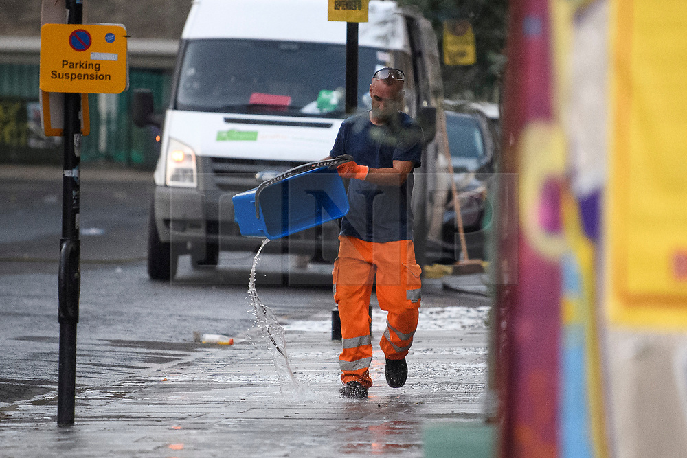 © Licensed to London News Pictures. 27/08/2019. London, UK. A worker washes the pavements in a street in Notting Hill, west London, in the aftermath of the 2019 Notting Hill carnival. The two day event is the second largest street festival in the world after the Rio Carnival in Brazil, attracting over 1 million people to the streets of West London. Photo credit: Ben Cawthra/LNP