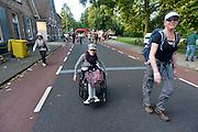 Nederland, Nijmegen, 15-7-2014 Start van de 98e 4 daagse. 43000 deelnemers. Op de Wedren worden de polsbandjes gescand waarna via het centrum en de  waalbrug gelopen wordt naar Bemmel en Elst in de Betuwe en wordt wel de dag van Elst genoemd. Op de foto de doorkomst in Bemmel. De vierdaagse is het grootste wandelevenement ter wereld.Rolstoel,rolstoeler, Foto: Flip Franssen/Hollandse Hoogte