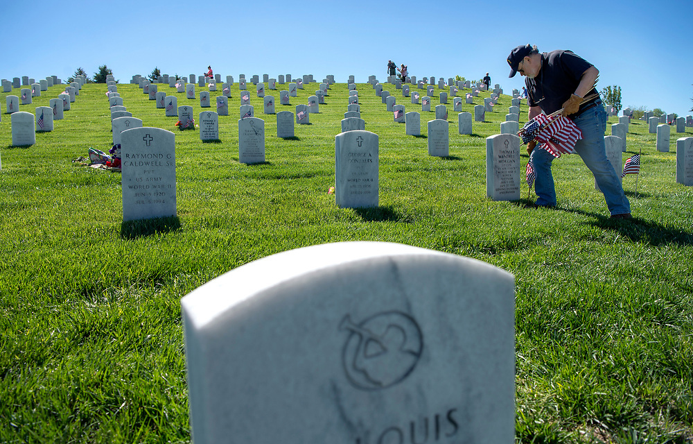 em052617b/a/Charles Green, from Los Alamos, plants flags on graves at the Santa Fe National Cemetery on Friday May 26, 2017. The flags on the over 58,000 graves at the cemetery will be there for the Memorial Day weekend as well as events on Monday. (Eddie Moore/Albuquerque Journal
