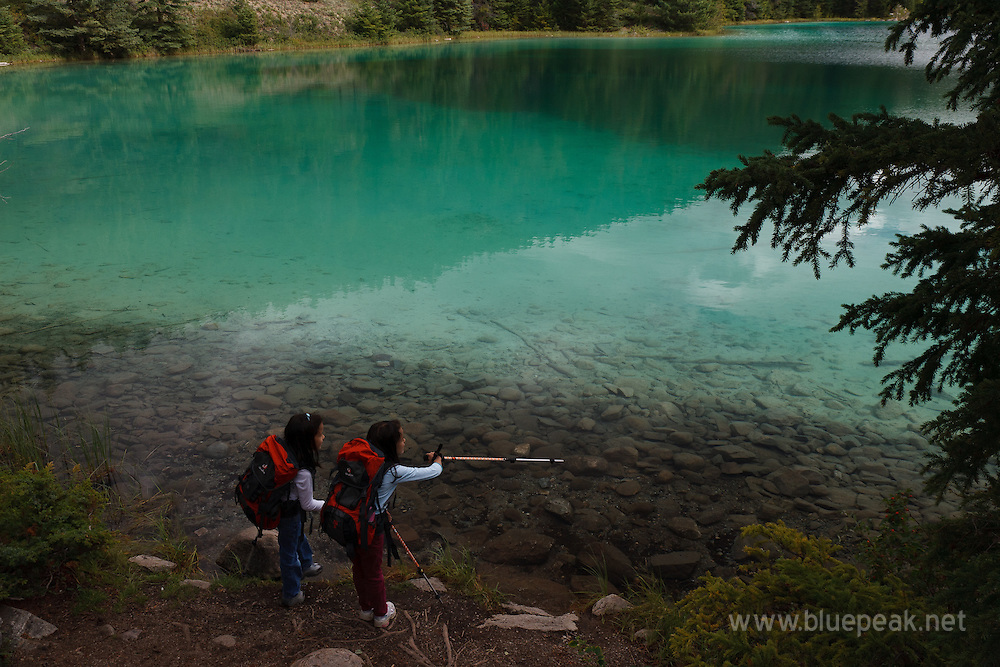 Girls pointing at an object at Valley of the Five Lakes, Jasper National Park, Canada