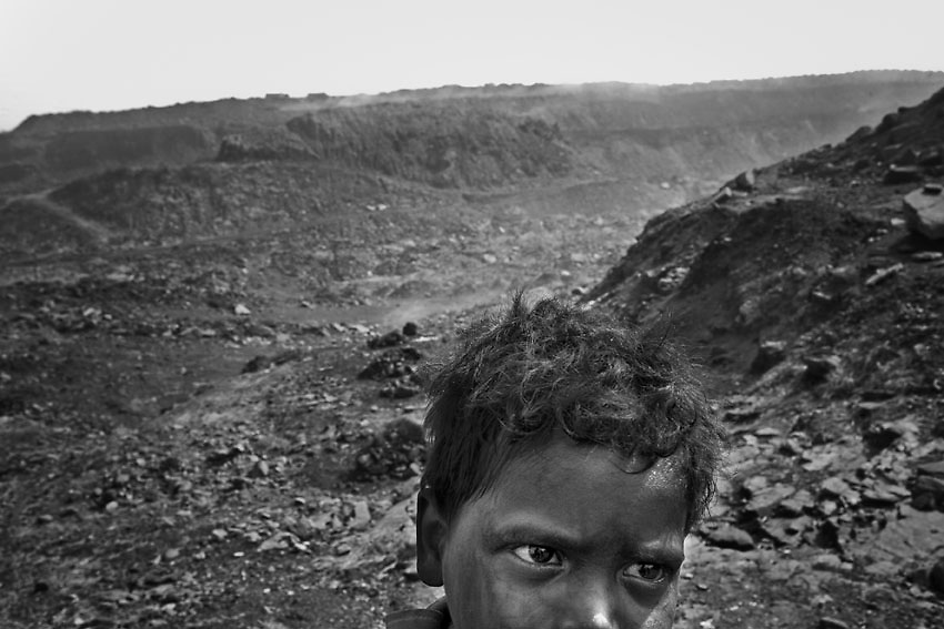 A child walks his way up to the Bokapahadi village after stealing coal from the mine nearby, Dhanbad, India.<br /> Here, due to the improper closure of abandoned mines and careless extraction techniques, the coal has been burning underground for a century. As soon as it turns to ashes, the ground collapses and the people are forced to move in shelters after the land has engulfed what remains of their burnt houses.<br /> Hand to mouth, they keep living in this wasteland, mostly surviving on the illegal sale of coal. In periods of more strict controls are the children, aged between four and eight years, to intercept the convoys leaving the mines to steal the coal that is then collected by other children and brought to the village.