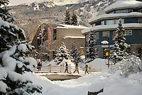Skiers stroll Whistler Village on a sunny winter day - here they walk over the bridge of Village Park, Millennium Place behind.
