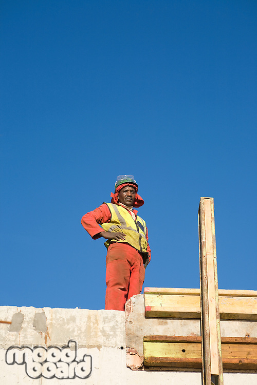 Construction worker stands with hands on hips on incomplete building
