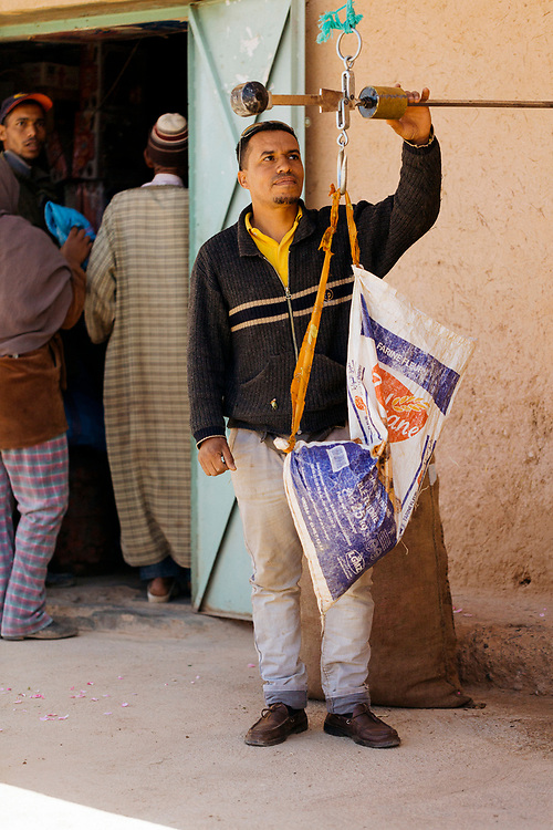KELAAT M'GOUNA, MOROCCO - 14TH MAY 2016 - A rose flower picker weighs their days yield at a traditional weighing scale next door to a local shop nearby to the rose fields in Kelaat M'Gouna, Dades Valley - also known as the 'Valley of Roses' - Southern Morocco.