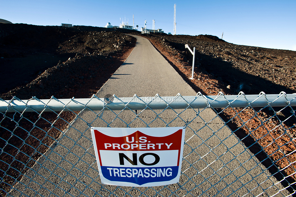 A U.S. Property No Trespassing sign and gate guard the entrance to the Mauna Loa Observatory, Hawaii.