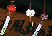 Glass wind chimes, known locally as Edo Furin, hand under the eaves outside Shinohara Furinhonpo in Tokyo, Japan. The traditional chimes, which were until not long ago carried around town by sellers on bamboo poles, date back more than 200 years in Japan. Today there are but a handful of makers left in Japan, with cheaper imports from Korea and China gaining the lion's share of the business for these popular summer decorations. Shinohara' Furinhonpo has been in operation for over 100 years. The family-run business makes around 200,000 of the chimes a year.