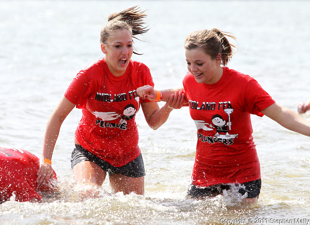 Paulina Baker (from left), 18, and Charli Arnell, 18, both of Midland High School make their way out of the water at the Polar Plunge event at Pleasant Creek State Recreation Area in Palo on Saturday March 26, 2011. 28 team participated in the event which was sponsored by local law enforcement agencies and raised money for Special Olympics Iowa.