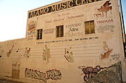 Urban decay, with razor wire and graffitti competing with a musical education. .Original Alamo Music Center Building, San Antonio, Texas, 2008
