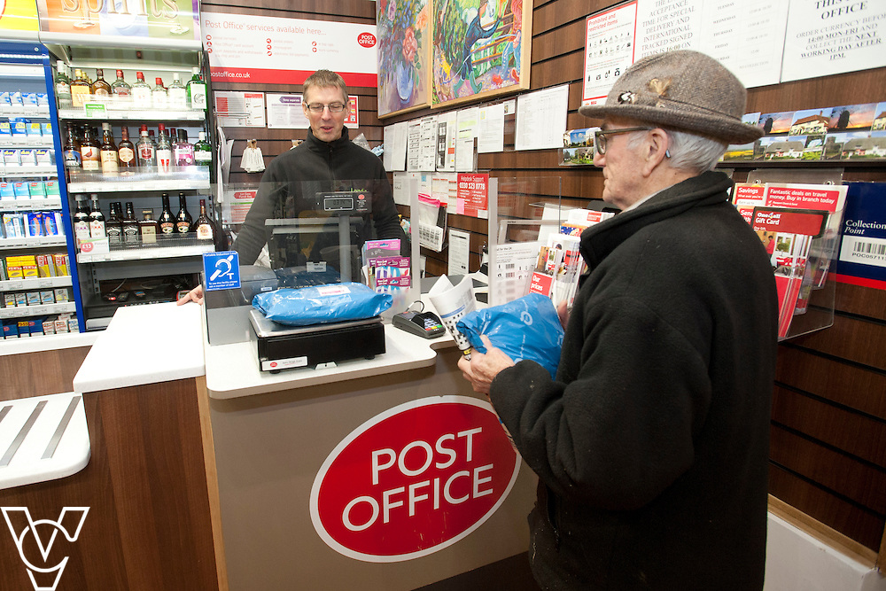 Pictured is postmaster Dave Bray serving customer Jim Foster<br /> <br /> Barley Post Office, Church End, Royston, Hertfordshire.<br /> Date: January 23, 2015