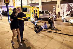 © licensed to London News Pictures. Manchester, UK 01/01/2012. New Years Day revellers in Manchester. A man collapses on the pavement in front of a bench and an ambulance, whilst others continue their night. Please see special instructions for usage rates. Photo credit should read Joel Goodman/LNP