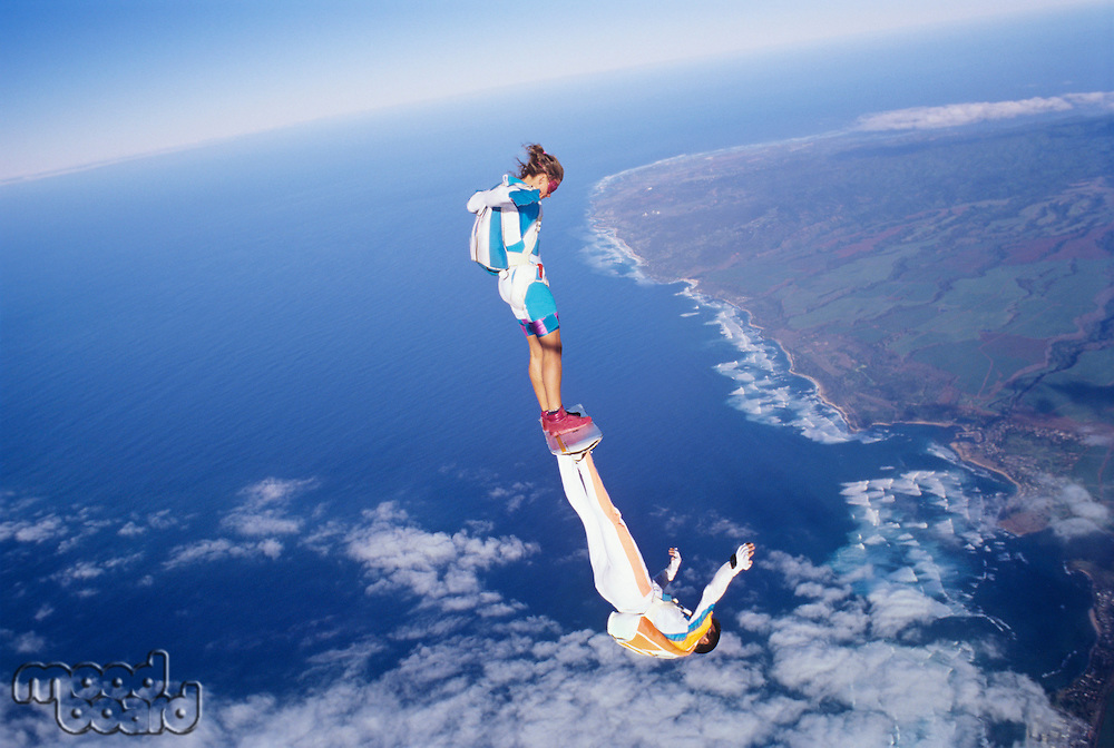 Two skydivers one upside down touching feet together