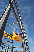 Welder working from cherry picker on warehouse construction