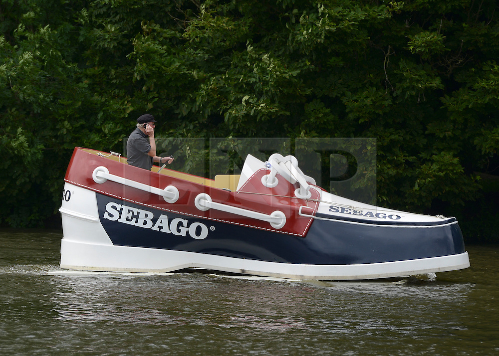 © Licensed to London News Pictures. 28/06/2012. Henley-on-Thames, UK A man steers a boat in the design of a shoe along the Thames. Spectators watch rowing crews compete at the Henley Royal Regatta on June 28, 2012 in Henley-on-Thames, England. The 173-year-old rowing regatta is held 27th June- 1st July 2012. Photo credit : Stephen Simpson/LNP