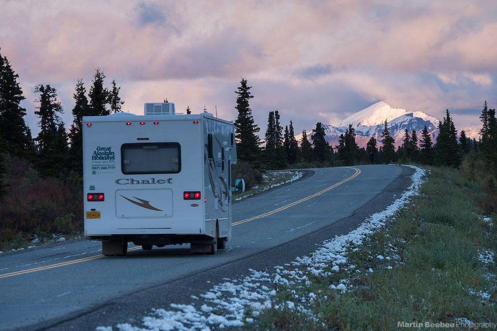 RV driving on the main road in Denali National Park at sunset, Alaska
